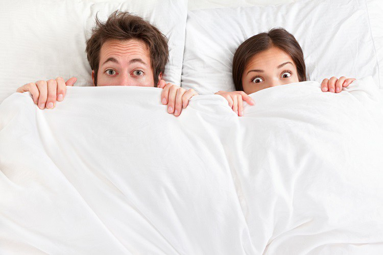 Funny couple in bed looking and peeking over sheets surprised. Young interracial couple, Asian woman, Caucasian man.